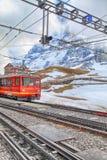 Järnvägsstationen med schweizaren utbildar och berg i Jungfrau, Swit Royaltyfri Fotografi