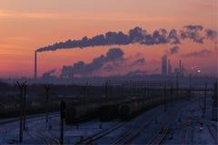 Järnvägstation Gasbearbetningsanläggning på horisonten Solnedgång Arkivbilder