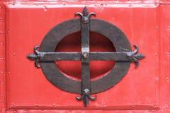 Järnverk på rött trä Royaltyfria Bilder