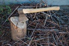 Järnyxa med ett trähandtag i ett träddäck royaltyfria foton