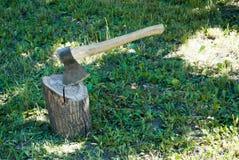 Järnyxa med ett trähandtag i ett träddäck arkivbild