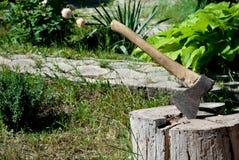 Järnyxa med ett trähandtag i ett träddäck arkivbilder
