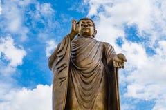 Jätte- guld- buddha som står scenisk i buddistiskt ställe Royaltyfri Foto