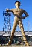 Jätte- guld- Drillerstaty och gränsmärke av oljefältarbetaren och den olje- borrtorn nära Route 66 i Tulsa Oklahoma royaltyfri bild