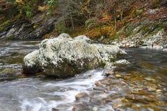 Jätte- stenblock i ström Arkivfoto
