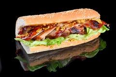 JätteBBQ Rib Sandwich med salladbladet och franska som är senapsgult i bagett Isolerat på en svart bakgrund arkivbild
