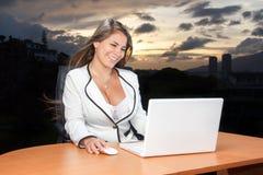 Jätteglad seende bärbar dator för affärskvinna i solnedgången Arkivbild
