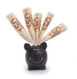 Jätteglad svart piggybank som är välfylld med 50 eurosedlar Royaltyfri Bild
