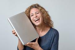 Jätteglad ung kvinna som rymmer en ny bärbar dator Royaltyfri Bild