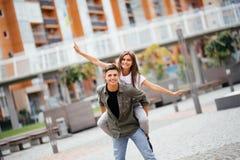 Jätteglade par som har en bra tid pargyckel som har le för par piggyback Arkivfoto