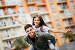 Jätteglade par som har en bra tid pargyckel som har le för par piggyback Royaltyfri Foto