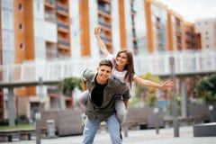 Jätteglade par som har en bra tid pargyckel som har le för par piggyback Royaltyfri Bild