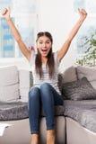 Jätteglat flickasammanträde på soffan Arkivbild
