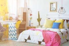 Jättestor säng i idérikt sovrum arkivbild