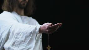 Jésus dans la robe longue atteignant la main avec la croix en bois sur le fond foncé banque de vidéos