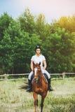 Jóquei da menina que monta um cavalo Imagens de Stock