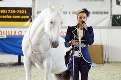 Jóquei equestre internacional da mulher da exposição e cavalo branco Durante a mostra Foto de Stock Royalty Free