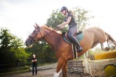 Jóquei fêmea novo no cavalo que pula sobre o obstáculo imagem de stock