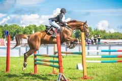 Jóquei novo, fêmea em seu cavalo que pula sobre um obstáculo Fotografia de Stock