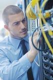 Jóvenes él ingeniero en sitio del servidor del datacenter imagenes de archivo