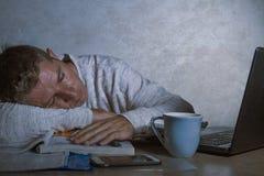 Jóvenes agotados y hombre soñoliento que trabaja en escritorio de la tensión en casa con paperwo que considera frustrado y cansad imagenes de archivo