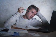 Jóvenes agotados y hombre soñoliento que trabaja en escritorio de la tensión en casa con paperwo que considera frustrado y cansad imagen de archivo