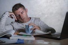 Jóvenes agotados y hombre soñoliento que trabaja en escritorio de la tensión en casa con paperwo que considera frustrado y cansad fotos de archivo libres de regalías