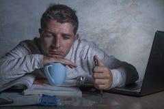 Jóvenes agotados y hombre soñoliento que trabaja en escritorio de la tensión en casa con paperwo que considera frustrado y cansad foto de archivo libre de regalías
