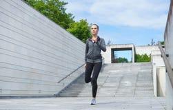 Jóvenes, ajuste y muchacha deportiva funcionando con para arriba las escaleras Aptitud, deporte, el activar urbano y concepto san Imágenes de archivo libres de regalías
