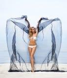 Jóvenes, ajuste y mujer hermosa en el baile de la playa con la seda Fotografía de archivo libre de regalías