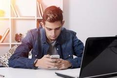 Jóvenes con el móvil y el ordenador portátil Imagen de archivo libre de regalías