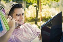 Jóvenes con el teléfono móvil y el ordenador portátil Foto de archivo