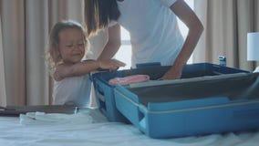Jóvenes con la pequeña hija que recoge una maleta junto almacen de video