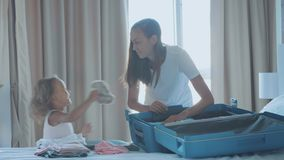 Jóvenes con la pequeña hija que recoge una maleta junto almacen de metraje de vídeo