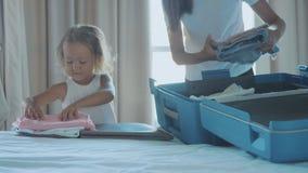 Jóvenes con la pequeña hija que recoge una maleta junto metrajes