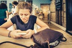 Jóvenes con un teléfono móvil en un café Imagen de archivo libre de regalías