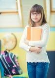 Jóvenes de la muchacha pre-adolescente hermosa con el folleto Un niño que hace la preparación Imágenes de archivo libres de regalías
