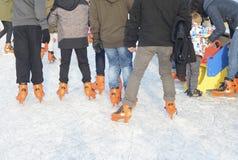 Jóvenes del patinaje de hielo en la pista de patinaje en patines de hielo anaranjados Imágenes de archivo libres de regalías
