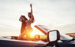 Jóvenes dos mujeres en una sesión fotográfica Muchachas con mucho gusto que presentan Imagen de archivo libre de regalías