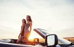 Jóvenes dos mujeres en una sesión fotográfica Muchachas con mucho gusto que presentan Fotografía de archivo libre de regalías