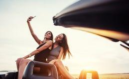 Jóvenes dos mujeres en una sesión fotográfica Muchachas con mucho gusto que presentan Imagen de archivo