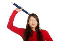Jóvenes hermosos con un lápiz grande en la cabeza Imagen de archivo