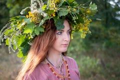 Jóvenes hermosos en un vestido de Viking Age y de la guirnalda de las hojas y de las flores del roble imagen de archivo libre de regalías