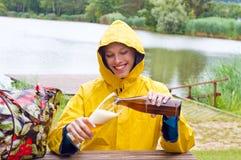 Jóvenes, mujer que bebe una cerveza del trigo en un día lluvioso Fotografía de archivo libre de regalías
