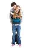 Jóvenes que abrazan los pares aislados en un blanco Imágenes de archivo libres de regalías