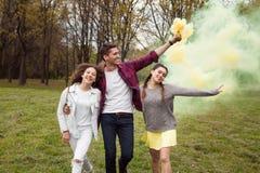 Jóvenes que caminan con humo coloreado en parque Fotos de archivo