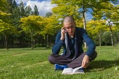 Jóvenes que leen un libro en un parque fotografía de archivo libre de regalías