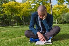 Jóvenes que leen un libro en un parque Fotos de archivo