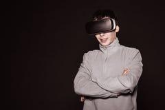 Jóvenes sorprendidos en el suéter gris, el hombre en los vidrios de realidad virtual Imagen de archivo