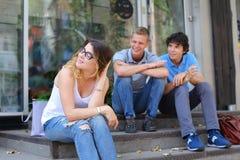 Jóvenes tres amigos que sientan el piso en la calle, hablando, con Foto de archivo libre de regalías